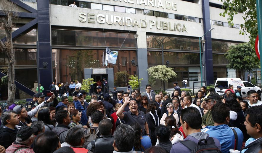 People who work inside an office of the Secretary of Public Security organize in the street as they collectively refuse to return to work inside the building which they say suffered internal damage in last week's 7.1 magnitude earthquake in Mexico City, Monday, Sept. 25, 2017. They are demanding independent inspectors confirm the building is safe before returning to work inside after the Sept. 19 quake. (AP Photo/Rebecca Blackwell)