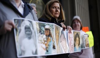 FILE - In this March 29, 2011, file photo, Barbara Blaine, President of Survivors Network of those Abused by Priests (SNAP), displays childhood photographs of adults who say they were sexually abused, during a news conference in Philadelphia. Barbara Blaine, the founder and former president of the Survivors Network of those Abused by Priests, has died. The organization known as SNAP announced on its Facebook page that Blaine died Sunday, Dept. 24, 2017, following a recent cardiac event. She was 61. (AP Photo/Matt Rourke, File)