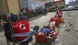 Residents line up gas cans as they wait for a gas truck to service an empty gas station, in the aftermath of Hurricane Maria in Loiza, Puerto Rico, Sunday, Sept. 24, 2017. Federal aid is racing to stem a growing humanitarian crisis in towns left without fresh water, fuel, electricity or phone service by the hurricane. (AP Photo/Gerald Herbert)