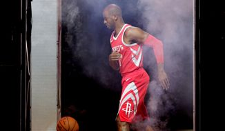 Houston Rockets' Chris Paul chases a basketball amid lighting and fog machines while he takes part in a promotional video shoot during an NBA basketball media day, Monday, Sept. 25, 2017, in Houston. (AP Photo/Michael Wyke)