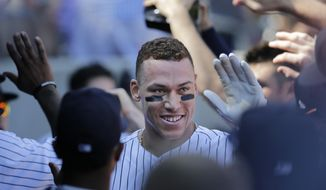 New York Yankees' Aaron Judge greets teammates in the dugout after hitting a two-run homer during the third inning of a baseball game against the Kansas City Royals at Yankee Stadium, Monday, Sept. 25, 2017, in New York. It was Judge's 49th home run, which ties the MLB rookie home run record. (AP Photo/Seth Wenig)