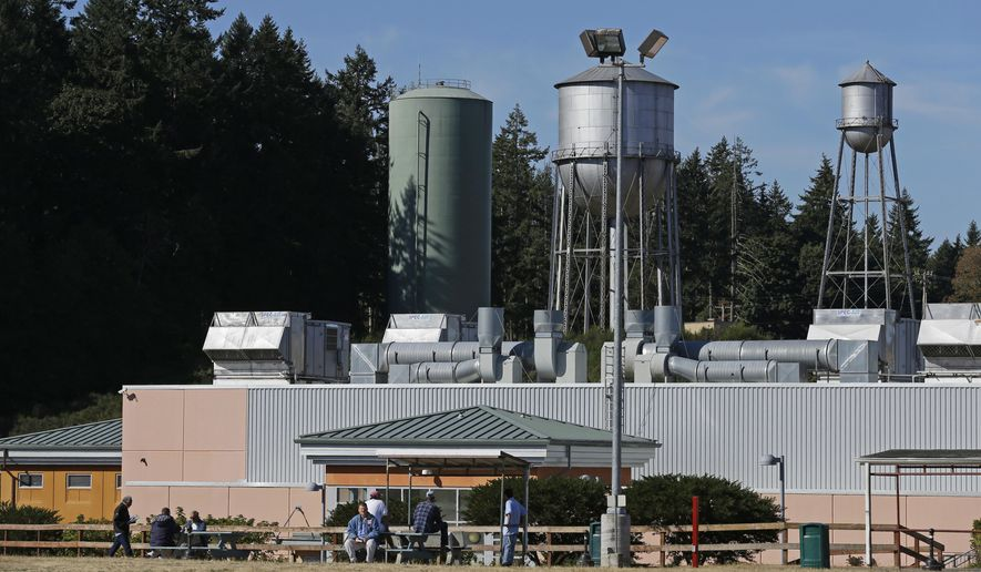 In this Sept. 15, 2017 photo, residents sit in a yard at the Special Commitment Center on McNeil Island, Wash., with the current water tower that serves the facility behind them at left, next to two older and currently unused towers. Scores of sex offenders ordered to live on the secluded island say the water there is making them sick and causing unexplained deaths, and records show the water system has been plagued by problems for more than a decade. (AP Photo/Ted S. Warren)