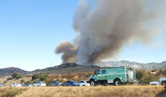 Authorities head to fight a wildfire near the Riverside County line in Anaheim Hills, Calif., Monday, Sept. 25, 2017. (Ken Steinhardt/The Orange County Register via AP)