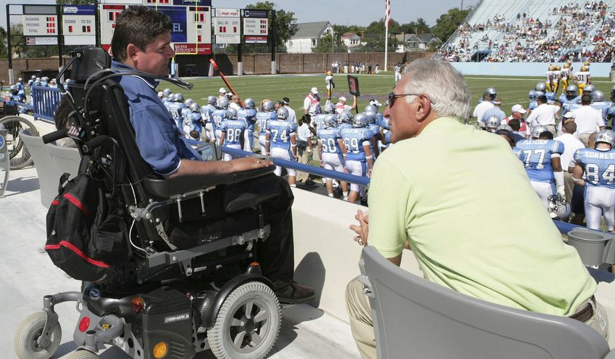 "FILE - In this Sept. 30, 2006, file photo, Marc Buoniconti, left, who was paralyzed from the neck down during a Citadel football game in 1985, watches the first half of Citadel's game against Chattanooga with his father Nick, right, as they wait for halftime, when his jersey was retired in Charleston, S.C., on Saturday, Sept. 30, 2006. Marc Buoniconti has been confined to a wheelchair for 32 years. Through those decades his father Nick has been his companion. Marc calls Nick his ""savior."" Now it is Nick who needs Marc's inspiration. (AP Photo/Alice Keeney, File)"
