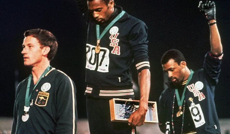 """FILE - In this Oct. 16, 1968, file photo, extending gloved hands skyward in racial protest, U.S. athletes Tommie Smith, center, and John Carlos stare downward during the playing of """"The Star-Spangled Banner"""" after Smith received the gold and Carlos the bronze medal in the 200 meter run at the Summer Olympic Games in Mexico City. Carlos and Smith staged one of the most iconic protests in sports history, when they raised their fists during the medals ceremony at the 1968 Olympics. They were sent home immediately by the U.S. Olympic Committee, which spent decades wrestling with how and whether the sprinters should be honored. The International Olympic Committee has rules against using the games for political statements, though Scott Blackmun of the U.S. Olympic Committee said, """"Our stance on this is fairly clear, and we recognize the rights of athletes to express themselves."""" (AP Photo/File)"""