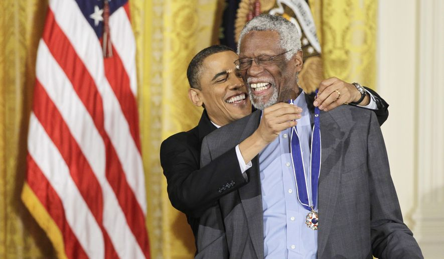 President Barack Obama reaches up to present a 2010 Presidential Medal of Freedom to basketball hall of fame member, former Boston Celtics coach and captain Bill Russell, Tuesday, Feb. 15, 2011, during a ceremony in the East Room of the White House in Washington. (AP Photo/Charles Dharapak) ** FILE **