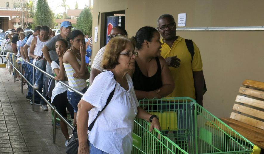 People wait in line outside a grocery store to buy food that wouldn't spoil and that they could prepare without electricity, in San Juan, Monday, Sept. 25, 2017. Most stores and restaurants remained closed Monday. Nearly all of Puerto Rico was without power or water five days after Hurricane Maria. (AP Photo/Ben Fox)