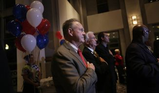 Former Alabama Chief Justice and U.S. Senate candidate Roy Moore, stops to say the Pledge of Allegiance as he walks around greeting supporters before his election party, Tuesday, Sept. 26, 2017, in Montgomery, Ala. (AP Photo/Brynn Anderson)