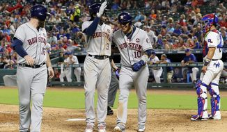 Houston Astros' Brian McCann (16), Cameron Maybin (3) and Yuli Gurriel (10) celebrate Maybin's three-run home run as they walk to the dugout past Texas Rangers catcher Robinson Chirinos in the sixth inning of a baseball game, Tuesday, Sept. 26, 2017, in Arlington, Texas. The shot came off a pitch from Rangers reliever Yohander Mendez. (AP Photo/Tony Gutierrez)