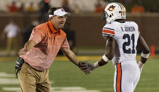 Auburn head coach Gus Malzahn, left, congratulates running back Kerryon Johnson, right, after he scored a touchdown during the third quarter of an NCAA college football game against Missouri Saturday, Sept. 23, 2017, in Columbia, Mo. (AP Photo/L.G. Patterson)