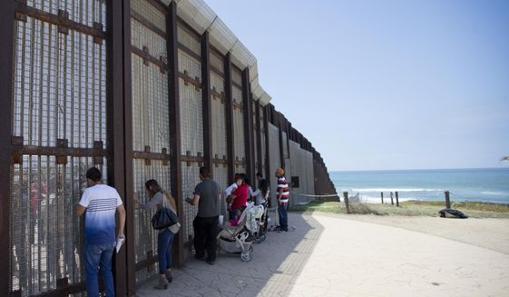 FILE- In this May 1, 2016, file picture, Eva Lara, second from let, reacts as she reaches for her grandmother Juana Lara through the border wall during a brief visitation near where Mexico and the United States meet at the Pacific Ocean in San Diego. The federal government said Tuesday, Sept. 26, 2017, that contractors began building eight prototypes of President Donald Trump's proposed border wall with Mexico, hitting a milestone toward a key campaign pledge. (AP Photo/Gregory Bull, File)