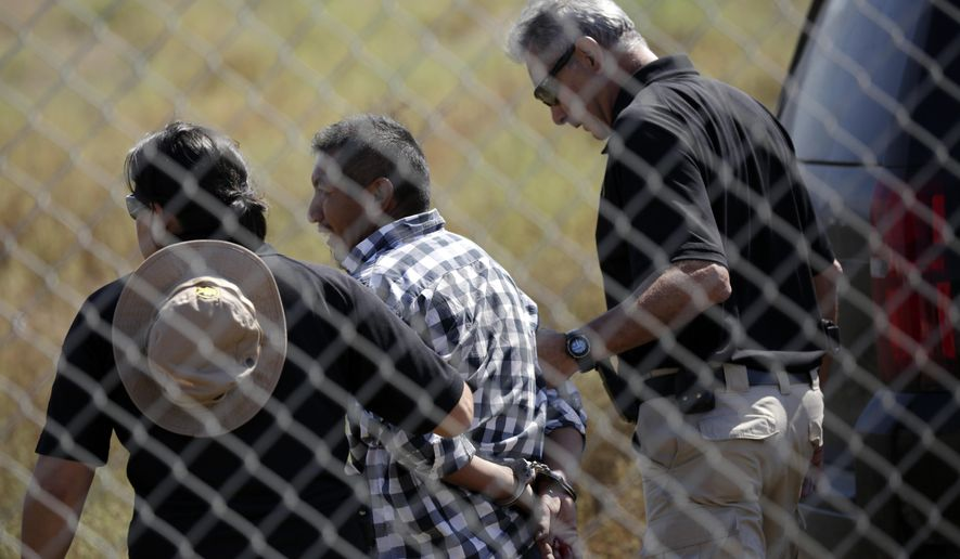 A man is detained by Border Patrol officials after breaching border fencing separating San Diego from Tijuana, Mexico, Tuesday, Sept. 26, 2017, in San Diego. The man, who said he was from Chiapas, Mexico, was detained by agents as they prepared for a news conference to announce that contractors have begun building eight prototypes of President Donald Trump's proposed border wall with Mexico. (AP Photo/Gregory Bull)