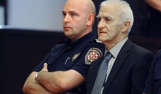 In this Tuesday, Sept. 20, 2016 file photo, Dragan Vasiljkovic, right, a former Serb paramilitary commander, sits next to a guard in a courtroom at the beginning of his trial in Split, Croatia. The municipal court has sentenced Vasiljkovic to 15 years in prison for war crimes in the 1990s Tuesday, Sept. 26, 2017. In the verdict it said that Vasiljkovic, also known as Captain Dragan and Daniel Snedden, is guilty of the killings and torture of imprisoned civilians and Croatian troops while he was a rebel Serb commander during the 1991-95 war in Croatia. (AP Photo, FILE)
