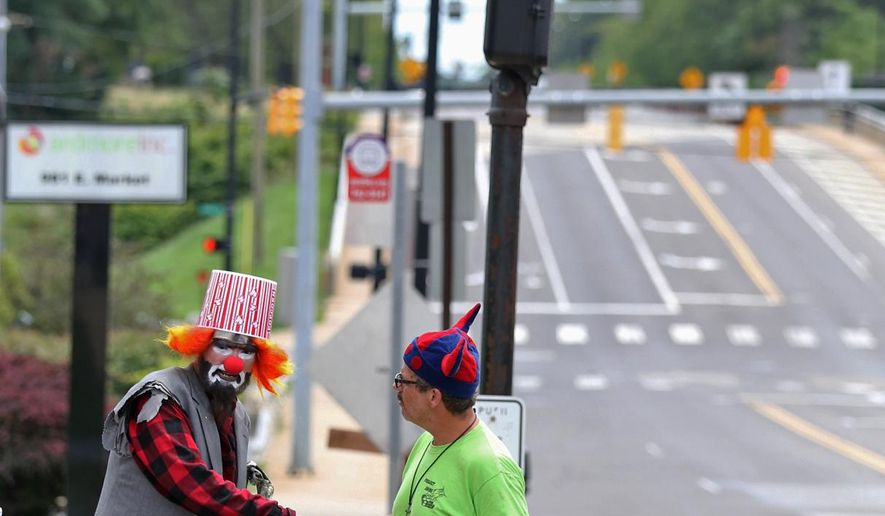 In this Sept. 6, 2017 photo, Ryan Scanlon, known as Skribblez the panhandler clown, gives lessons on the art of panhandling to Richard Cline from curbside in Akron, Ohio. (Phil Masturzo/Akron Beacon Journal via AP)