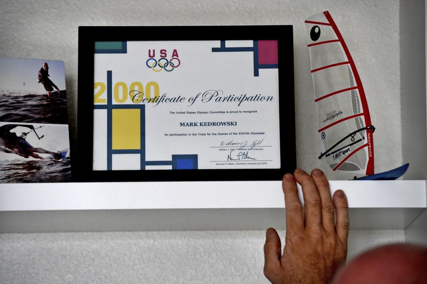In this Sept. 6, 2017 photo, Mark Kedrowski looks over a framed Certificate of Participation from the 1999 Olympic Trials in his White Bear Lake, Minn. home. In 1999, he qualified for the U.S. Olympic Trials in windsurfing. Kedrowski, 46, was nearly killed in 2010 when the plane he was piloting crashed shortly after takeoff from the Lake Elmo airport. Kedrowski, who said the plane was losing power before the crash, sued the designer of the plane's fuel pump, Lycoming Engines, and its manufacturer, Kelly Aerospace Power Systems. A jury awarded him $27.7 million in the case, which was then overturned by a judge. Kedrowski has filed an appeal with the Minnesota Court of Appeals. (Jean Pieri /Pioneer Press via AP)