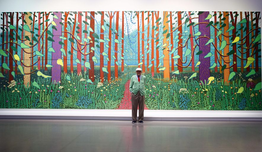 """Renowned British painter David Hockney poses during the unveiling of a huge painting he is donating to the Pompidou Center in Paris, """"The Arrival of Spring in Woldgate, East Yorkshire."""", in Paris, France, Tuesday, Sept. 26, 2017. The 2011 painting includes 32 panels stretching more than 3 meters high and nearly 10 meters wide, and goes on display this week as part of a traveling retrospective of the 80-year-old Hockney's work. (AP photo/Francois Mori)"""