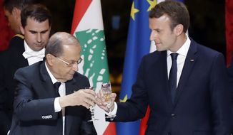 Lebanese President Michel Aoun, left, and French President Emmanuel Macron make a toast during a dinner at the Elysee Palace in Paris, France, Monday, Sept. 25, 2017. (Etienne Laurent/Pool Photo via AP)