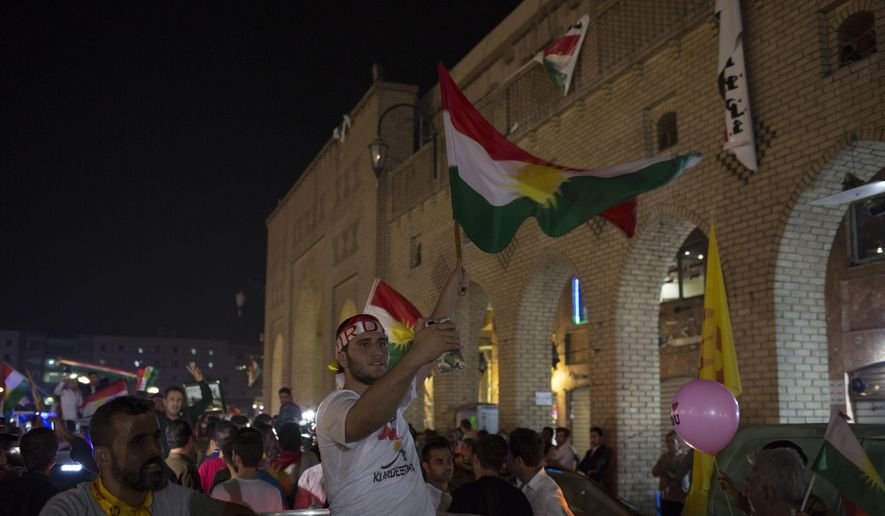A man waves the Kurdish flag in the streets of Irbil after polling stations closed on Monday, Sept. 25, 2017. The Kurds of Iraq were voting in a referendum on support for independence that has stirred fears of instability across the region, as the war against the Islamic State group winds down. (AP Photo/Bram Janssen)