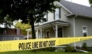 Police tape surrounds the house that was the scene of a shooting in Lennox, S.D., Tuesday, Sept. 26, 2017. The shooting, which left three dead including an eight-year-old boy, is being investigated as a murder-suicide according to the Lincoln County Sheriff's office. (Sam Caravana/The Argus Leader via AP)