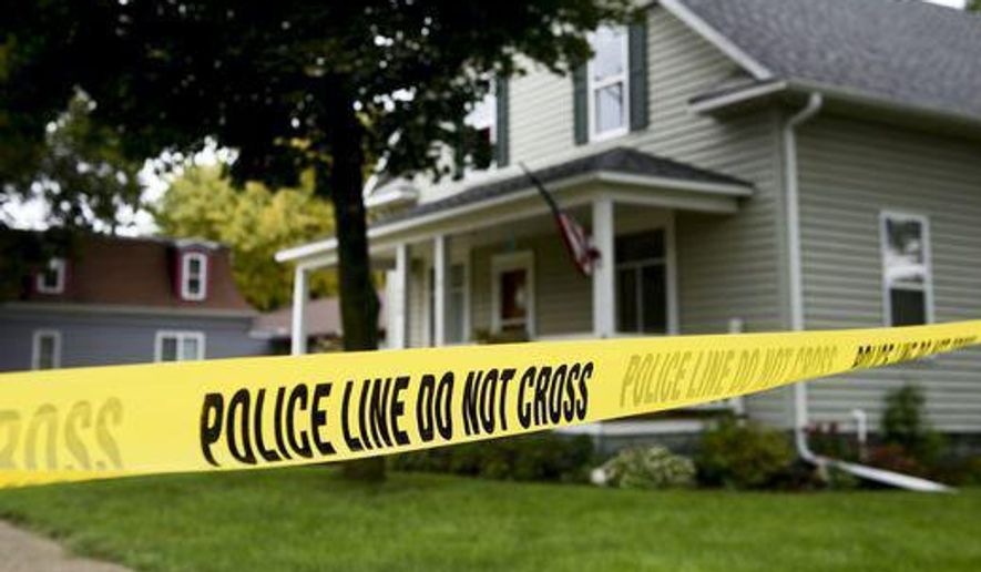 In this file photo, police tape surrounds the house that was the scene of a deadly shooting in Lennox, S.D., Tuesday, Sept. 26, 2017. (Sam Caravana/The Argus Leader via AP)  **FILE**