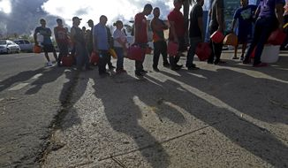 People wait in line for gas, in the aftermath of Hurricane Maria, in Aibonito, Puerto Rico, Monday, Sept. 25, 2017. The U.S. ramped up its response Monday to the humanitarian crisis in Puerto Rico while the Trump administration sought to blunt criticism that its response to Hurricane Maria has fallen short of it efforts in Texas and Florida after the recent hurricanes there. (AP Photo/Gerald Herbert)