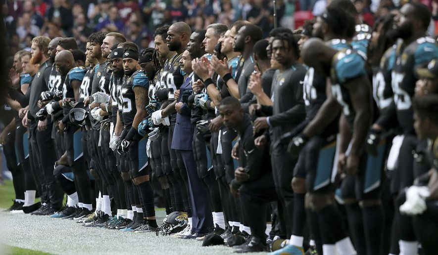 Jacksonville Jaguars owner Shahid Khan, center, joins arms with players as some kneel down during the playing of the U.S. national anthem before an NFL football game against the Baltimore Ravens at Wembley Stadium in London, Sunday Sept. 24, 2017. (AP Photo/Tim Ireland)