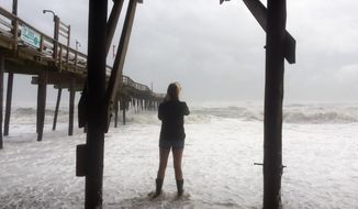 A woman stands in the water as Hurricane Maria moves closer to North Carolina's Outer Banks on Tuesday, Sept. 26, 2017. Thousands of visitors abandoned their vacation plans and left the area as the hurricane moved northward in the Atlantic, churning up surf and possible flooding. (AP Photo/Ben Finley)