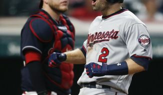 Minnesota Twins' Brian Dozier (2) celebrates after hitting a three run home run off Cleveland Indians relief pitcher Bryan Shaw as catcher Roberto Perez looks on during the eighth inning in a baseball game, Tuesday, Sept. 26, 2017, in Cleveland. (AP Photo/Ron Schwane)