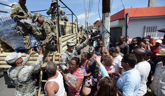 National Guardsmen arrive at Barrio Obrero in Santurce to distribute water and food among those affected by the passage of Hurricane Maria, in San Juan, Puerto Rico, Sunday, Sept. 24, 2017. Puerto Rico's nonvoting representative in the U.S. Congress said Sunday that Hurricane Maria's destruction has set the island back decades, even as authorities worked to assess the extent of the damage. (AP Photo/Carlos Giusti)