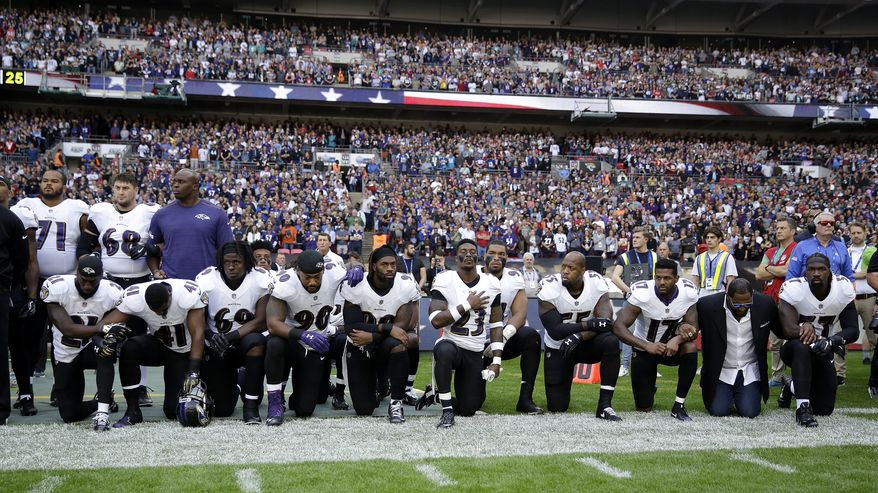 FILE - In this Sunday Sept. 24, 2017 file photo, Baltimore Ravens players, including former player Ray Lewis, second from right, kneel down during the playing of the U.S. national anthem before an NFL football game against the Jacksonville Jaguars at Wembley Stadium in London. Joey Odoms, a combat veteran who has been the Ravens' national anthem singer for the past three years, announced his resignation as debate continues about players kneeling during the national anthem. (AP Photo/Matt Dunham, File)