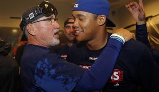 Chicago Cubs manager Joe Maddon, left, and shortstop Addison Russell celebrate after defeating the St. Louis Cardinals in a baseball game to clinch the National League Central title Wednesday, Sept. 27, 2017, in St. Louis. (AP Photo/Jeff Roberson)