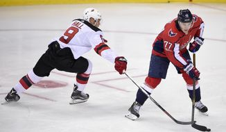 Washington Capitals right wing T.J. Oshie (77) skates with the puck past New Jersey Devils left wing Taylor Hall (9) during the third period of an NHL preseason hockey game, Wednesday, Sept. 27, 2017, in Washington. The Devils won 4-1. (AP Photo/Nick Wass)