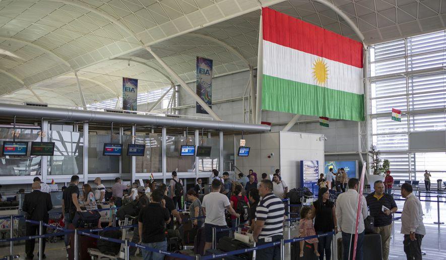 Travelers line up to check in at the Irbil International Airport, in Iraq, Wednesday, Sept. 27, 2017. Iraq's prime minister ordered the country's Kurdish region to hand over control of its airports to federal authorities or face a flight ban, a response to the Kurdish independence referendum. (AP Photo/Bram Janssen)