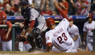 Philadelphia Phillies' Aaron Altherr, right, scores past Washington Nationals catcher Pedro Severino on a two-run double by Jorge Alfaro during the second inning of a baseball game, Wednesday, Sept. 27, 2017, in Philadelphia. (AP Photo/Matt Slocum)