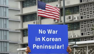 """A South Korean protester holds up a card during a rally to denounce the United States' policy against North Korea in front of U.S. Embassy in Seoul, South Korea, Wednesday, Sept. 27, 2017. North Korea's top diplomat said Monday that a weekend tweet by U.S. President Donald Trump was a """"declaration of war"""" and North Korea has the right to retaliate by shooting down U.S. bombers, even in international airspace. (AP Photo/Ahn Young-joon)"""