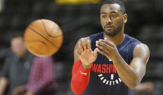 Washington Wizards guard John Wall reaches for  ball as he practices free throws at NBA basketball training camp in Richmond, Va., Wednesday, Sept. 27, 2017. (AP Photo/Steve Helber)