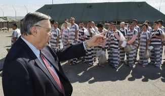 FILE - In this Feb. 4, 2009, file photo, Maricopa County Sheriff Joe Arpaio, left, orders approximately 200 convicted illegal immigrants handcuffed together and moved into a separate area of Tent City, for incarceration until their sentences are served and they are deported to their home countries, in Phoenix. An audit report produced in a racial profiling case against the Maricopa County Sheriff's Office says Hispanics are more likely to be searched and arrested by sheriff's deputies in traffic stops than white people. The report was issued nearly four years after a judge ordered a sweeping overhaul of then-Sheriff Joe Arpaio's office after concluding officers had racially profiled Hispanics in immigration patrols. (AP Photo/Ross D. Franklin, File)