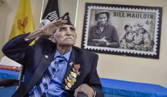 In a Sept. 23, 2017 photo,  Joe Romero salutes General Kenneth A. Nava after he is presented with the Bronze Star as well as other medals in Albuquerque, N.M. Romero is a Bataan Death March survivor. He was surrounded by his family Saturday as he also celebrated his 97th birthday at the New Mexico Vietnam Veterans Visitor Center in Albuquerque. (Roberto E. Rosales/The Albuquerque Journal via AP)