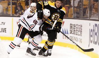Boston Bruins left wing Matt Beleskey tries to get away from Chicago Blackhawks' John Hayden (40) during the first period of an NHL preseason hockey game in Boston, Monday, Sept. 25, 2017. (AP Photo/Winslow Townson)
