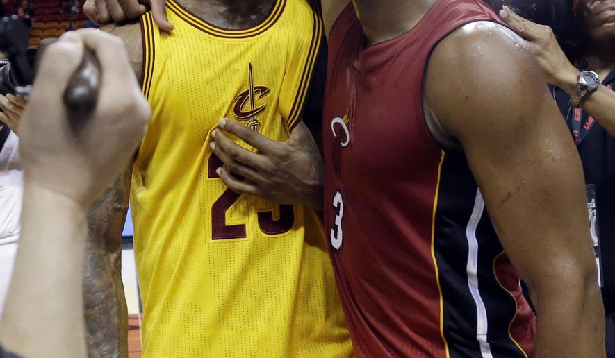 FILE - In this Dec. 25, 2014, file photo, Cleveland Cavaliers forward LeBron James (23) and Miami Heat guard Dwyane Wade talk following an NBA basketball game in Miami. Wade is expected to sign Wednesday, Sept. 27, 2017, with the Cavaliers, reuniting the 12-time All-Star with James, a former Miami teammate and one of his best friends.  (AP Photo/Lynne Sladky, File)
