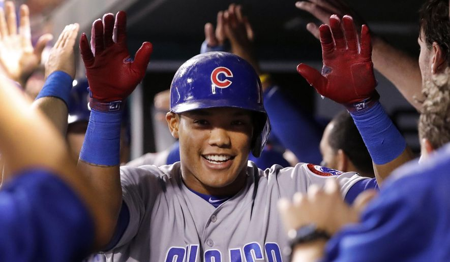 Chicago Cubs' Addison Russell is congratulated by teammates in the dugout after hitting a three-run home run during the seventh inning of a baseball game against the St. Louis Cardinals Wednesday, Sept. 27, 2017, in St. Louis. (AP Photo/Jeff Roberson)