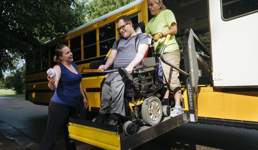 In this June 20, 2017 photo, direct support professional Cat McNamara jokes with Jimmy Mossow as he is lifted on to the bus to go to work outside of the Diane Road Group Home in Mendota Heights, Minn. Diane Road offers residents stability, emotional connection and a sense of control over their own lives. But everyone who lives at Diane Road has their own personality, preferences and medical needs. Caregivers have to keep all of this information handy, and it means things can get complicated quickly.  (Evan Frost  /Minnesota Public Radio via AP)