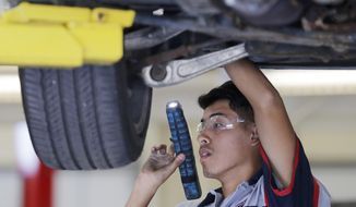 In this Thursday, Sept. 14, 2017 photo, Green Bay East senior Eric Cardona inspects the underside of a car during a City Stadium Automotive class at East High School, in Green Bay, Wis. The class is part of the Turbocharge with College Credit initiative, launched earlier this year in Green Bay Public schools. (Adam Wesley/The Post-Crescent via AP)