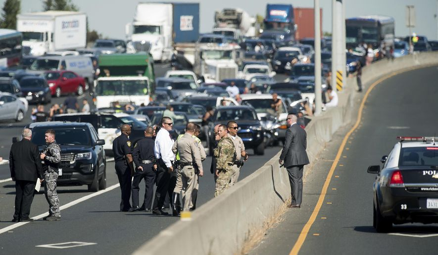 Police officers investigate the scene of a standoff with a suspect driving a sports utility vehicle on westbound Interstate 80 on Wednesday, Sept. 27, 2017, in Emeryville, Calif. The incident, which ended in gunfire, shut freeway traffic in both directions at the height of morning rush hour. (AP Photo/Noah Berger)