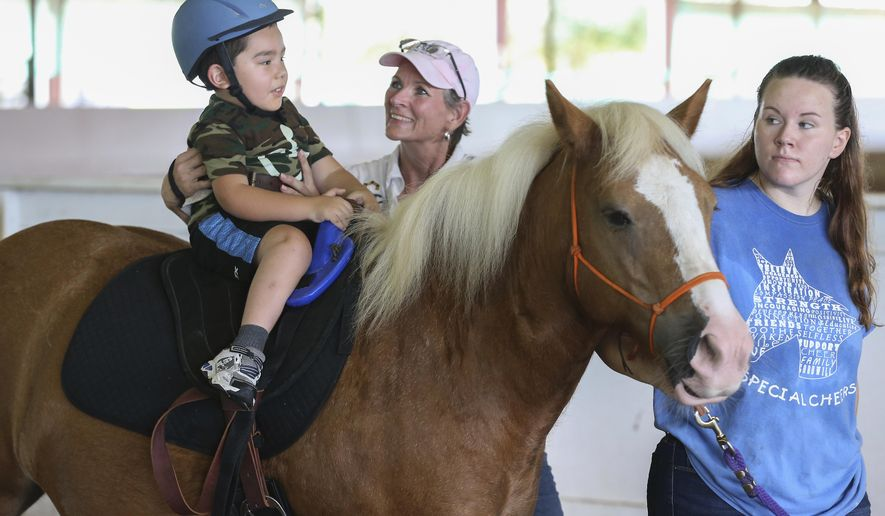 "In this Tuesday, Sept. 19, 2017, photo, Fritzi Glover-Strowmatt, left, reassures Alexander Lowery, 6, as Aurali Glover, right, leads ""CoCo"" during a session of therapeutic horseback riding with the nonprofit Special CHEERS in Katy. Their facility was flooded during Harvey, so the Great SW Equestrian Center site is housing their horses until they can get back to classes. (Steve Gonzales/Houston Chronicle via AP)"