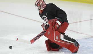 In this photo taken Friday, Sept. 15, 2017, Carolina Hurricanes goalie Scott Darling deflects a shot during the NHL hockey team's training camp in Raleigh, N.C. (AP Photo/Gerry Broome)