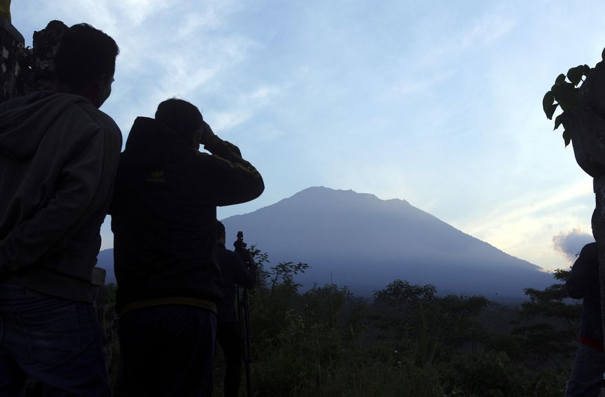 Villagers watch Mount Agung from an observation point which is about 12 kilometer (7.4 miles) away from the volcano in Karangasem, Bali, Indonesia, Thursday, Sept. 28, 2017. The exodus from the menacing volcano on the Indonesian tourist island is nearing 100,000 people, a disaster official said Wednesday, as hundreds of tremors from the mountain are recorded daily. (AP Photo/Firdia Lisnawati)