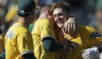 Oakland Athletics' Mark Canha, right, is embraced after hitting a walk off home run off Seattle Mariners' Shae Simmons in the ninth inning of a baseball game Wednesday, Sept. 27, 2017, in Oakland, Calif. (AP Photo/Ben Margot)