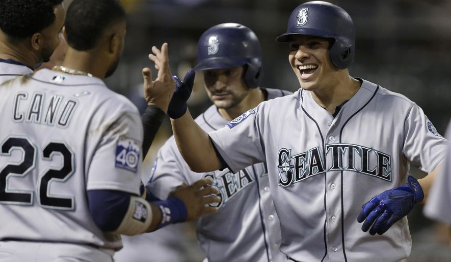 Seattle Mariners' Danny Valencia, right, celebrates with Robinson Cano (22) after hitting a three-run home run off Oakland Athletics' Ryan Dull during the seventh inning of a baseball game Tuesday, Sept. 26, 2017, in Oakland, Calif. (AP Photo/Ben Margot)