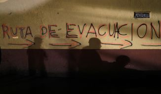 "Shadows of rescue workers and volunteers are cast on the wall of an apartment building covered with the spray painted words in Spanish: ""Evacuation route"" in the southern neighborhood of Tlalpan in Mexico City, Monday, Sept. 25, 2017. The 7.1 magnitude quake on Sept. 19 left the complex's 500 residents, mostly government employees, without a home after one of the 11 buildings collapsed and the others were damaged. (AP Photo/Natacha Pisarenko)"